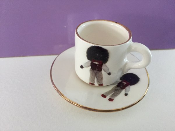 Miniature cup and saucer with Golliwog