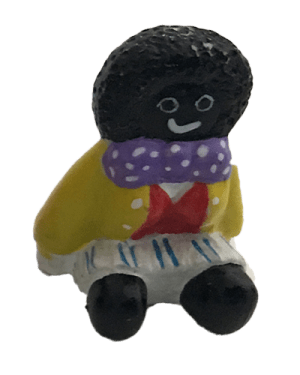 Miniature female golliwog sitting in yellow jacket